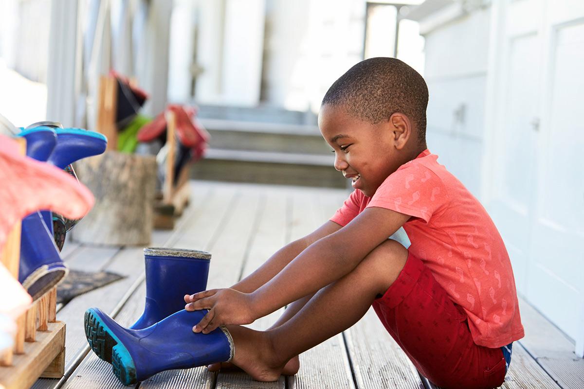 Un enfant qui met tout seul sa botte